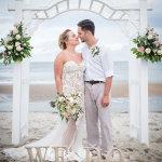 06-couple-kissing-under-arch-beach-wedding-emerald-isle-nc