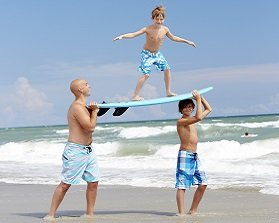 boy-on-surfboard-at-beach-279x223