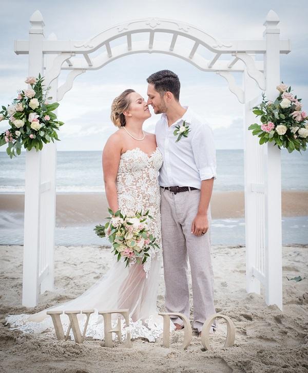 Couple kissing under arch during beach wedding in Emerald Isle, North Carolina