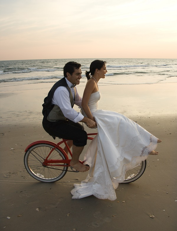 Couple Riding Bike on the Beach after Wedding