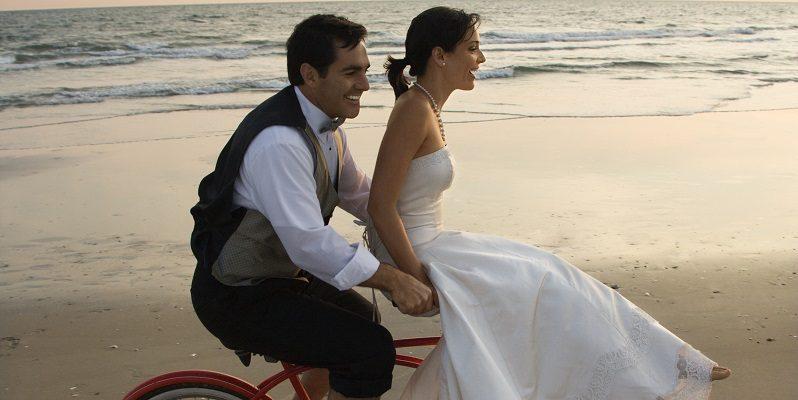 Wedding couple riding bike on beach