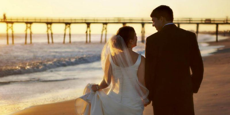 Bride and groom on beach by pier in emerald isle, NC