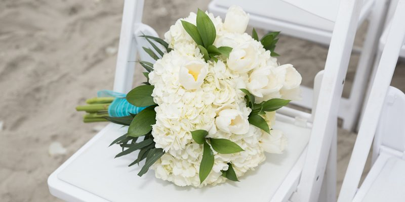 Beach wedding setup white flowers on white chair in emerald isle nc